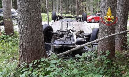 Perde il controllo dell'auto che finisce rovesciata in mezzo agli alberi